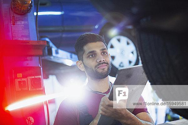 Männlicher Mechaniker mit Zwischenablage  der in einer Autowerkstatt arbeitet