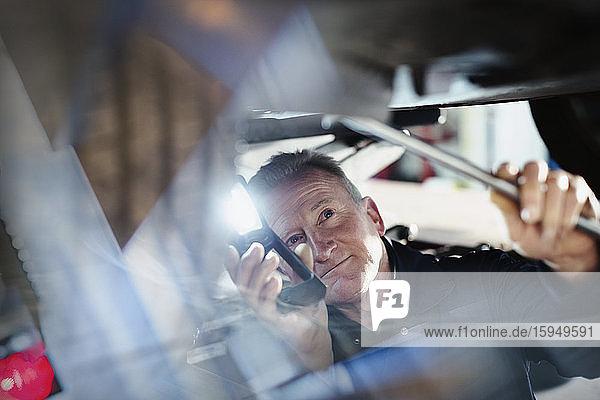 Männlicher Mechaniker mit Taschenlampe arbeitet unter dem Auto in einer Autowerkstatt