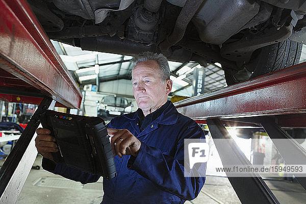 Männlicher Mechaniker benutzt Diagnosegerät unter Auto in Autowerkstatt