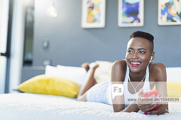 Lächelnde junge Frau entspannt auf dem Bett  hört Musik mit mp3-Player und Kopfhörern