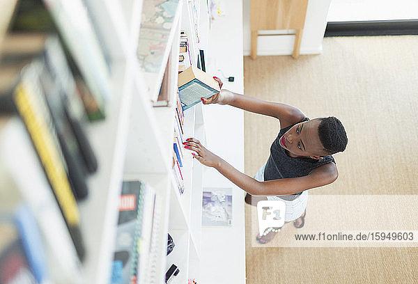 Junge Frau greift nach Buch im Bücherschrank