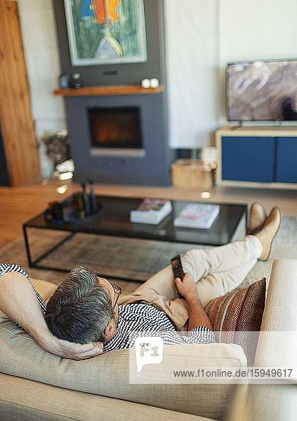 Mann entspannt sich  sieht auf dem Wohnzimmersofa fern