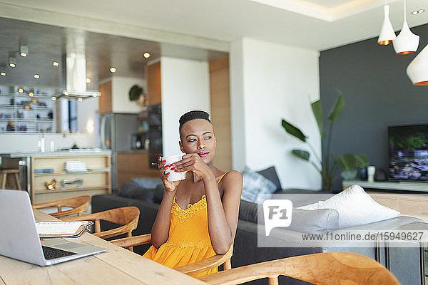 Nachdenkliche junge Frau  die Kaffee trinkt und von zu Hause aus am Laptop im Esszimmer arbeitet