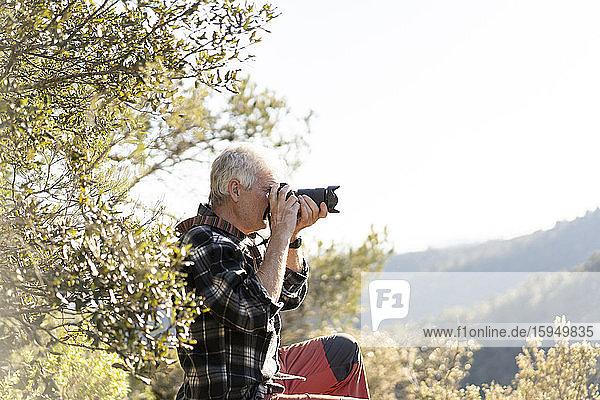 Älterer Mann beim Fotografieren in der Natur
