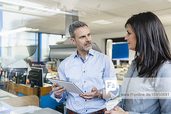 Geschäftsmann mit Tablette und Geschäftsfrau bei einem Arbeitstreffen in einer Fabrik
