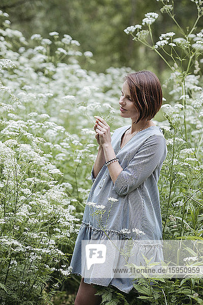 Thoughtful pregnant woman amidst flowering plants in park