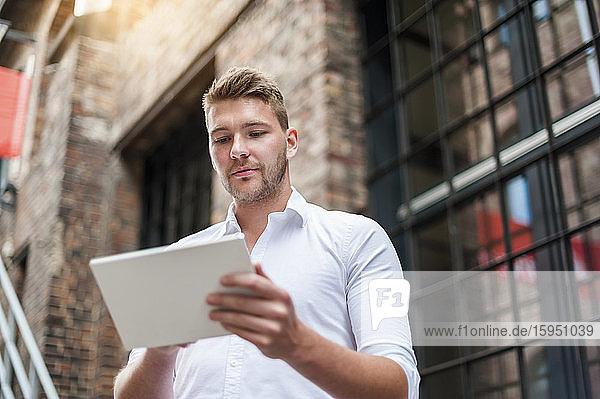 Junger Geschäftsmann benutzt Tablette in einem Backsteingebäude