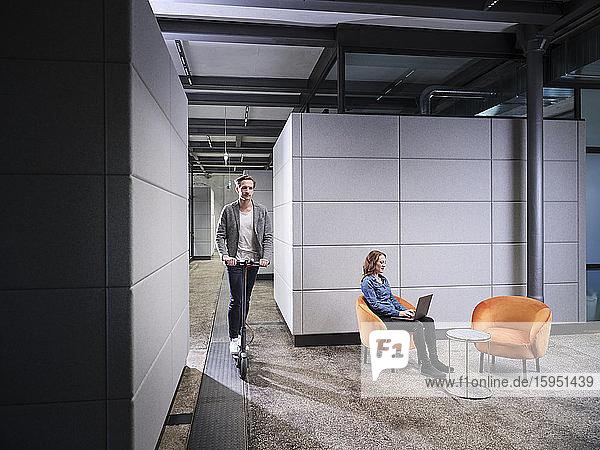 Geschäftsfrau sitzt im Sessel in einem modernen Büro mit Laptop und einem Kollegen auf einem Elektroroller