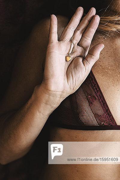 Nahaufnahme einer älteren Frau mit ihrem herzförmigen Halskettenanhänger
