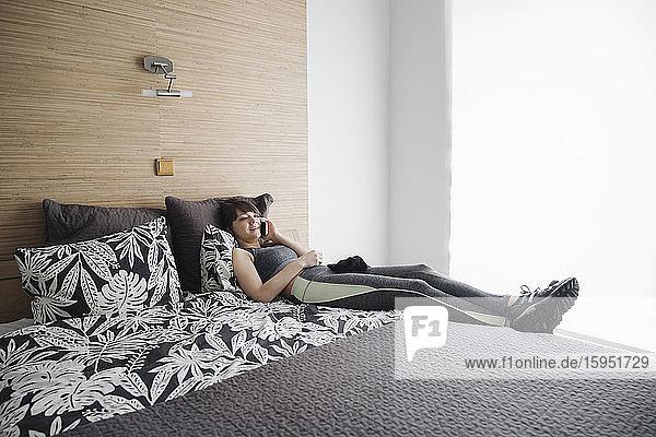 Frau  die nach dem Training zu Hause mit einem Smartphone auf dem Bett liegt