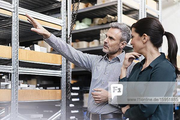 Geschäftsmann und Geschäftsfrau bei einer Arbeitsbesprechung im Lager einer Fabrik
