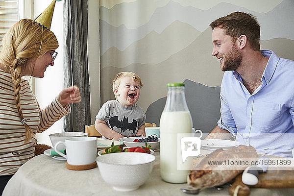 Porträt eines kleinen Jungen  der sich mit seinen Eltern am Frühstückstisch vergnügt