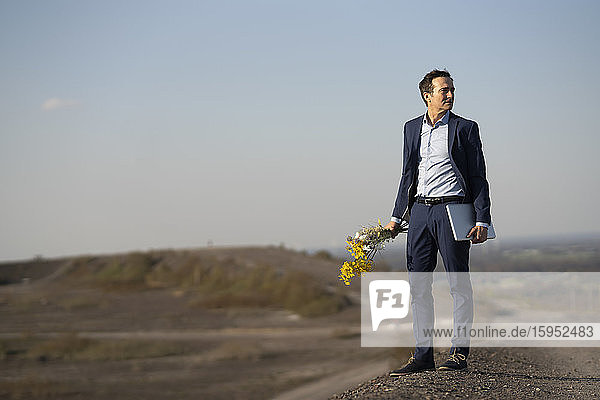 Mature businessman holding bunch of flowers and laptop on a disused mine tip