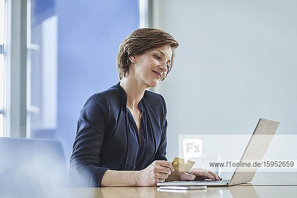 Lächelnde Geschäftsfrau mit Kreditkarte und Laptop am Schreibtisch im Büro Lächelnde Geschäftsfrau mit Kreditkarte und Laptop am Schreibtisch im Büro