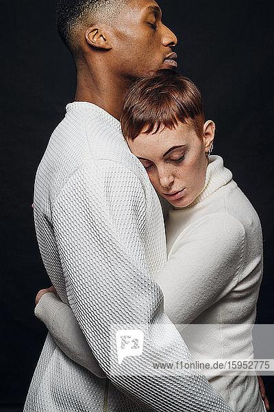 Studioporträt eines liebevollen gemischtrassigen Paares  das sich umarmt