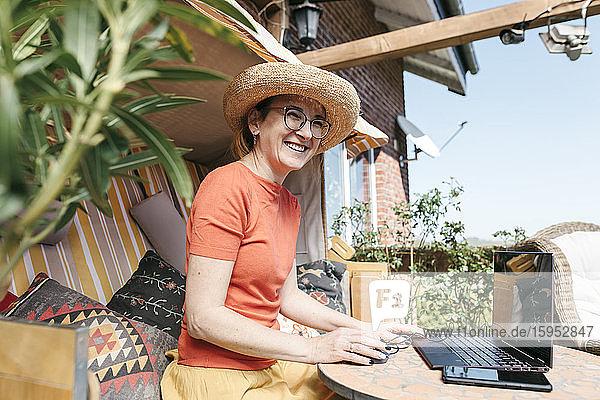 Porträt einer lachenden  reifen Frau  die am Laptop auf der Terrasse arbeitet