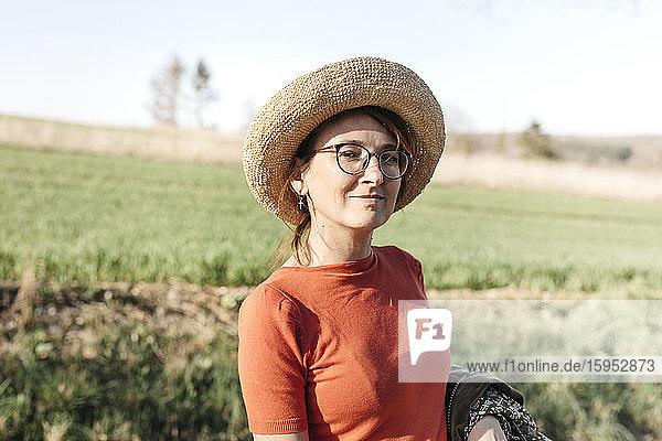 Porträt einer reifen Frau mit Brille und Strohhut in der Natur