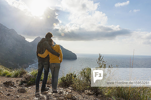 Back view of couple standing arm in arm looking to the sea  Mallorca  Spain