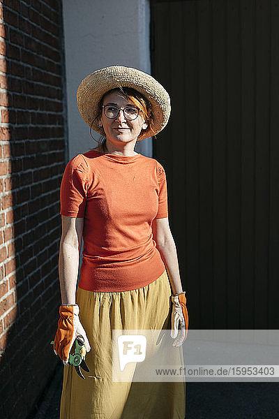 Bildnis einer reifen Frau mit Gartenhandschuhen und Baumschere im Sonnenlicht stehend
