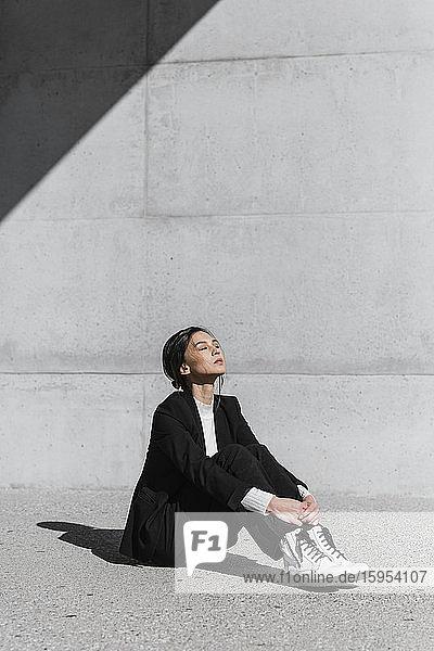 Junge Frau im schwarzen Anzug sitzt auf dem Boden vor einer Betonwand