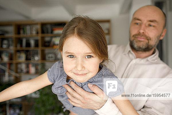 Vater spielt mit der Tochter und tut so  als würde er fliegen