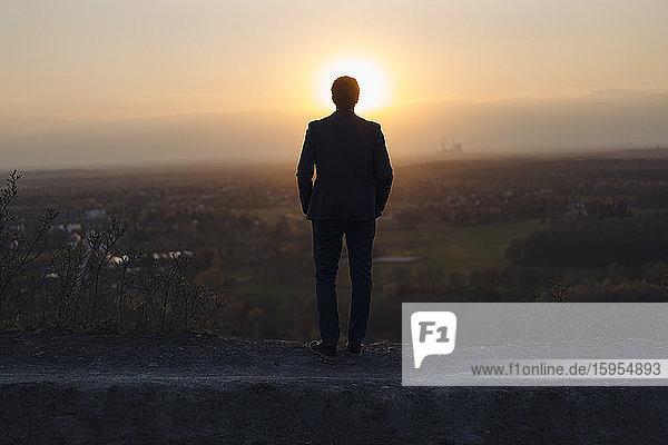 Ein reifer Geschäftsmann  der bei Sonnenuntergang auf einer stillgelegten Minenhalde steht und auf die Aussicht schaut