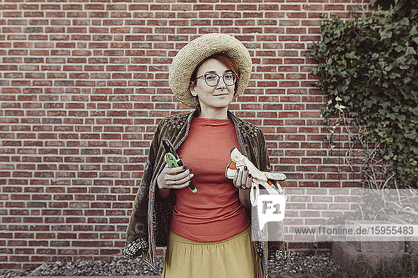 Porträt einer reifen Frau mit Gartenhandschuhen und Baumschere vor einer Ziegelmauer stehend