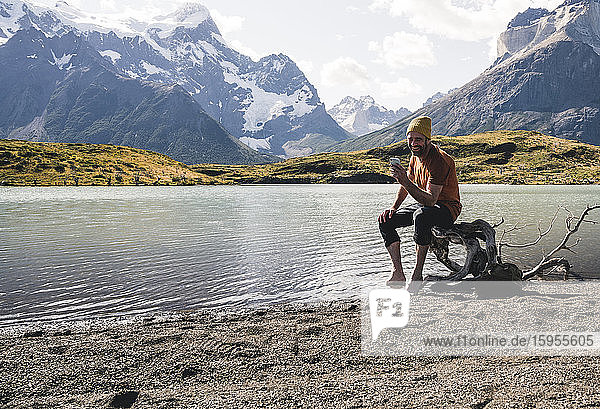 Man using cell phone in mountainscape at lakeside in Torres del Paine National Park  Patagonia  Chile
