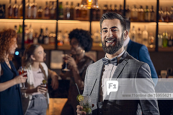 Porträt eines glücklichen jungen Mannes bei einem Cocktail in einer Bar Porträt eines glücklichen jungen Mannes bei einem Cocktail in einer Bar