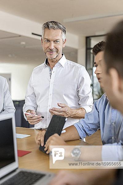 Ein reifer Geschäftsmann leitet eine Sitzung im Amt