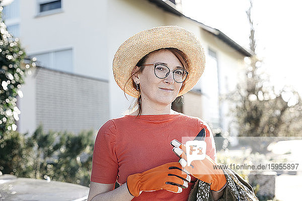 Porträt einer reifen Frau mit Scherenschneider mit Strohhut und Gartenhandschuhen