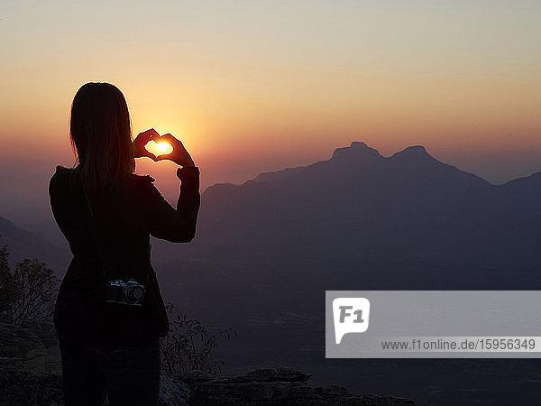 Silhouette einer Frau  die bei Sonnenuntergang mit ihren Händen das Herz formt  Serra da Leba  Angola