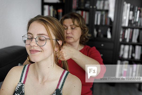 Porträt einer lächelnden jungen Frau mit geschlossenen Augen bei ihrer Mutter zu Hause