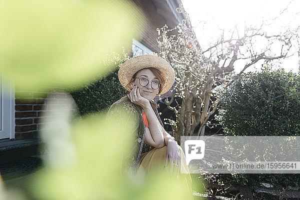 Porträt einer lächelnden reifen Frau mit Strohhut vor einem Einfamilienhaus sitzend