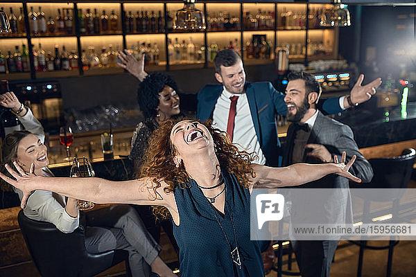 Überschwängliche junge Frau mit Freunden tanzt in einer Bar Überschwängliche junge Frau mit Freunden tanzt in einer Bar