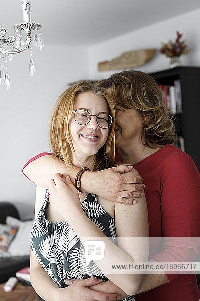 Mutter umarmt ihre erwachsene Tochter zu Hause