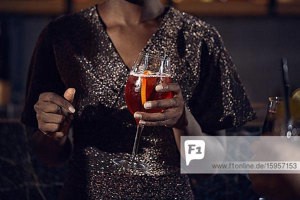Nahaufnahme einer Frau  die in einer Bar ein Cocktailglas hält Nahaufnahme einer Frau, die in einer Bar ein Cocktailglas hält