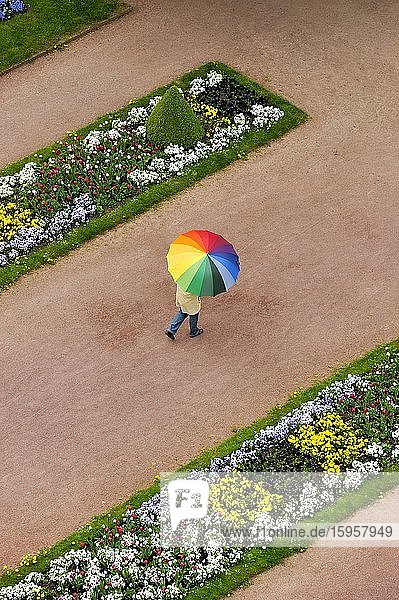 Person with an umbrella in rainbow colours on a red dirt road between flowerbeds in the Palace Gardens  Stadtschloss City Palace  Fulda  Hesse  Germany  Europe