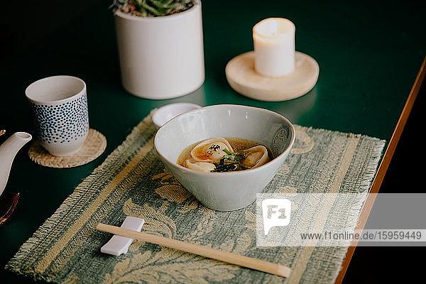 Nahaufnahme einer Schüssel Suppe mit Knödeln in einem Restaurant in Ramen und Gyoza in Italien.