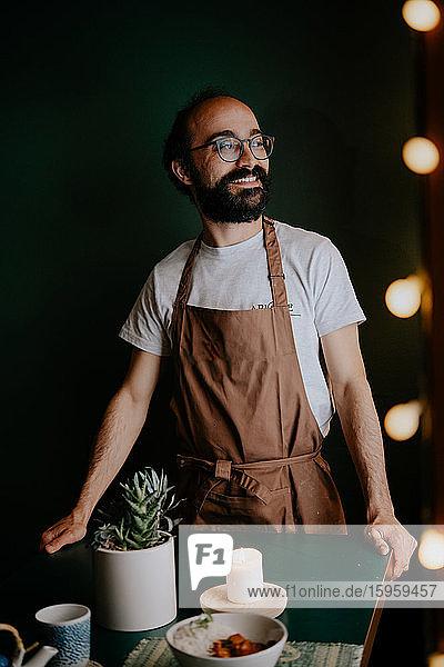 Porträt eines bärtigen Küchenchefs mit Schürze und Brille in einem Restaurant in Ramen und Gyoza in Italien.