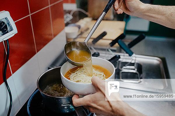 Nahaufnahme des Küchenchefs bei der Zubereitung einer Schüssel Ramen-Nudelsuppe in einem Ramen- und Gyoza-Restaurant in Italien.
