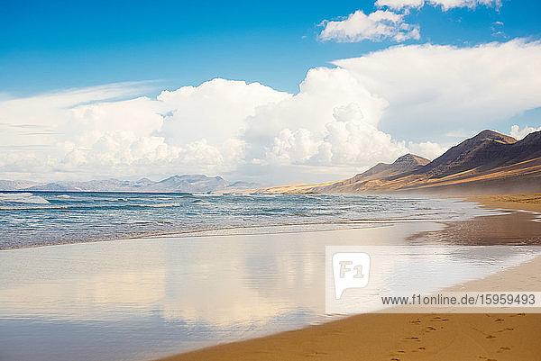 Blick entlang eines Sandstrandes auf Fuerteventura an einem bewölkten Tag.