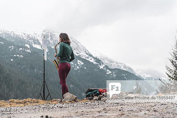 Frau  die auf einem Berg im Squamish Valley  British Columbia  Kanada  steht und Saxophon spielt.