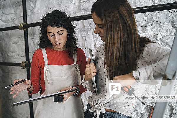 Two mid adult women checking plans and measurements in their new shop
