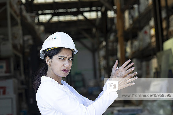 Female architect wearing white hard hat working on construction site  looking at camera.