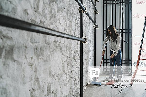 Mid adult woman sweeping floor in her new shop