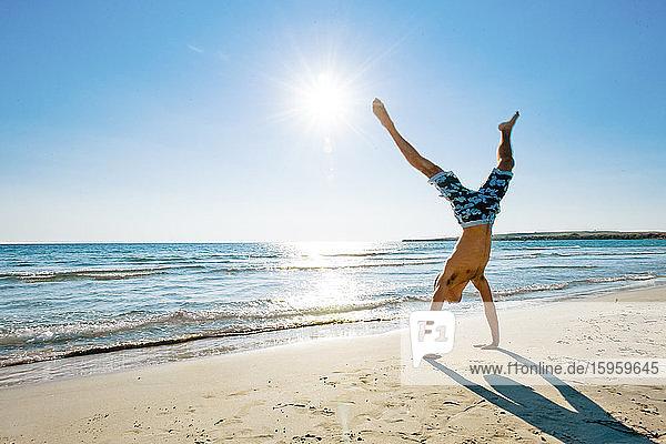 Man wearing swimming shorts doing cartwheel on sandy beach in Mediterranean.