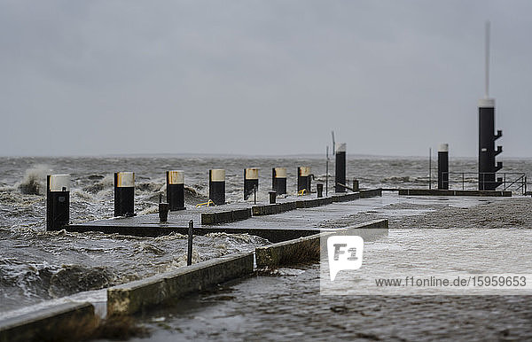 Storm battering a jetty at high tide at the Wadden Sea nature reserve in Friesland  The Netherlands.