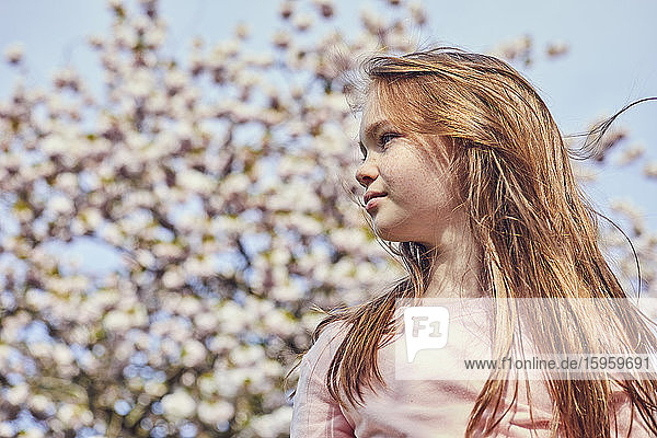 Portrait of brunette girl standing outdoors  tree with pink blossoms in background.