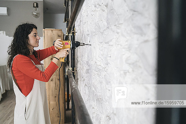 Mid adult woman drilling wall in her new shop